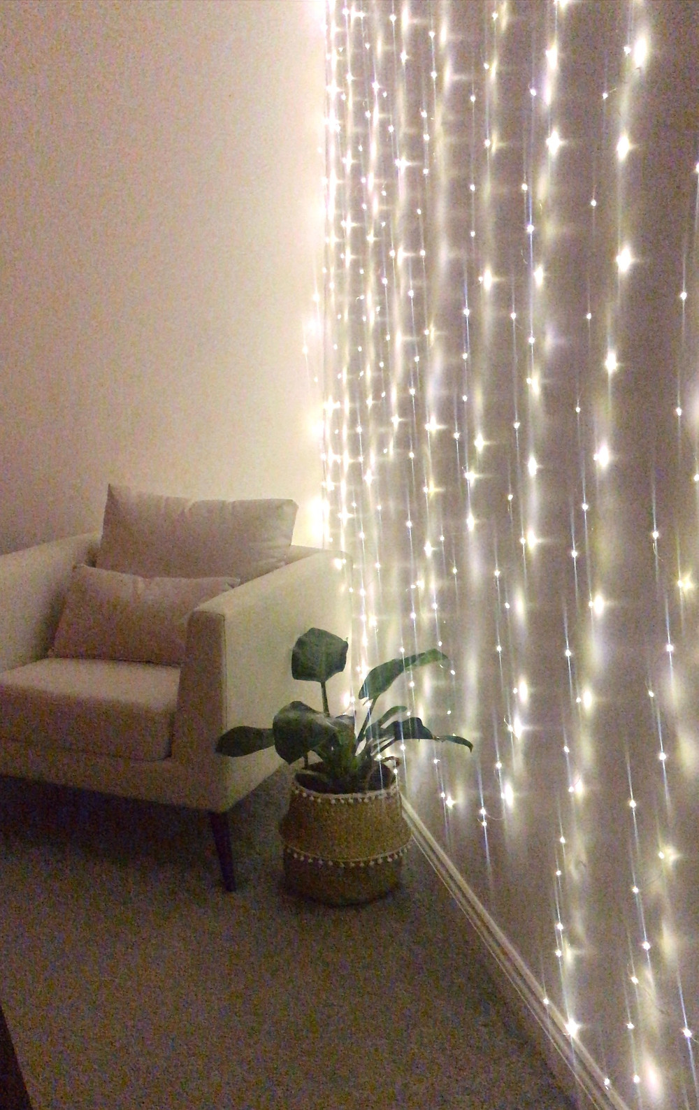 Fairy lit wall with beige arm chair and plant in a basket pot besides it