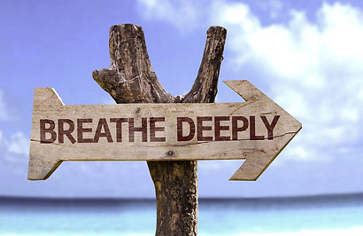Breathe Deeply sign attached to tree by ocean background