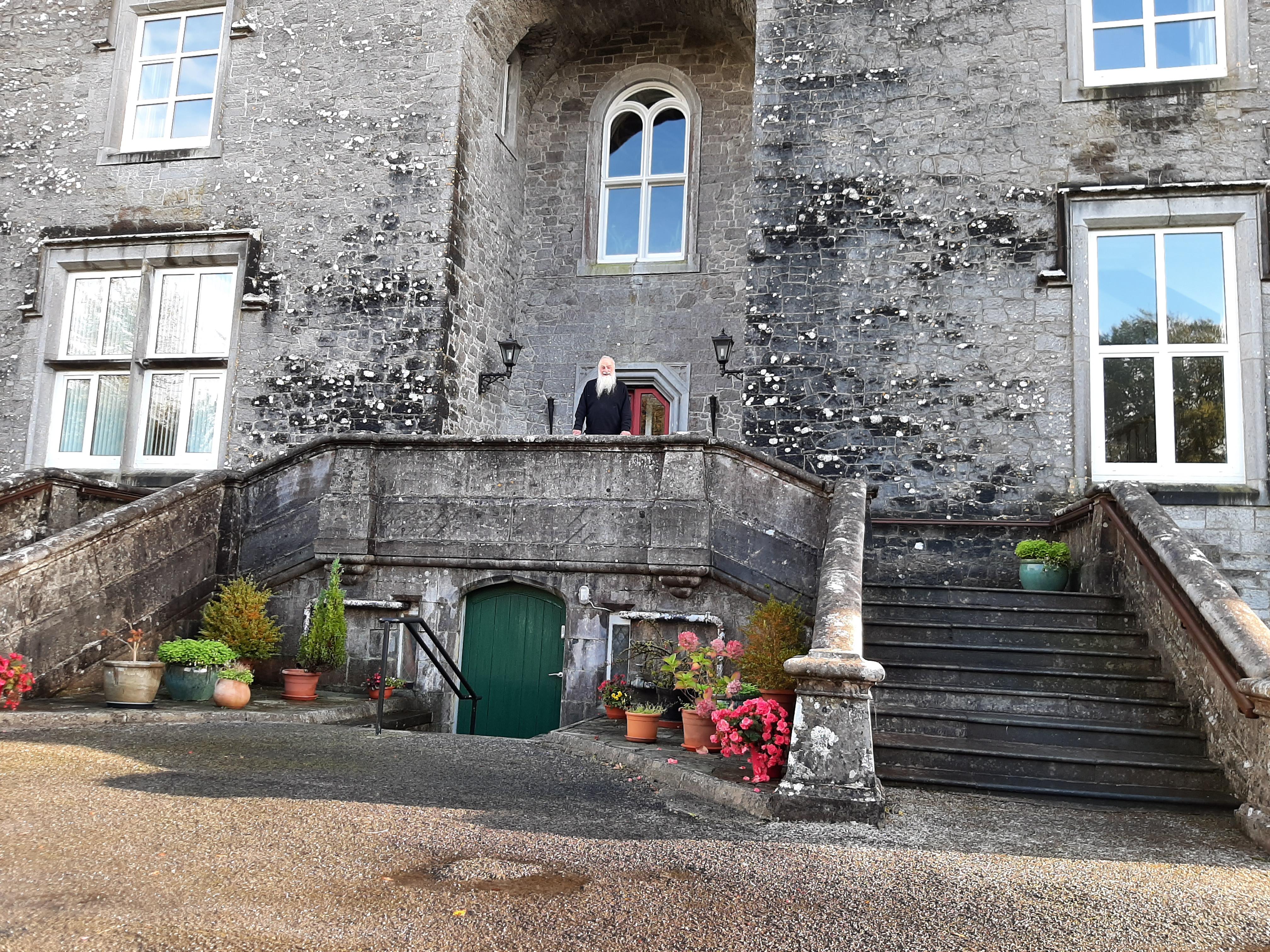 Fr Norman at front door of castle