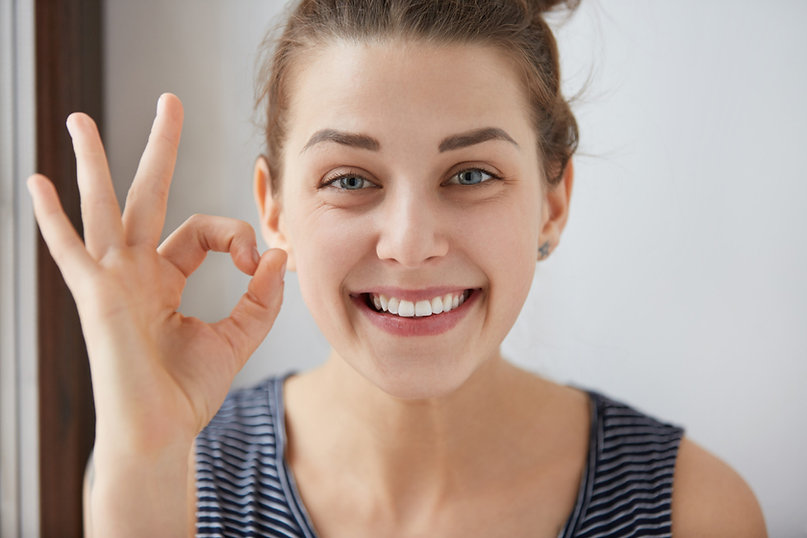 young-european-brunette-female-showing-ok-gesture-with-her-fingers-happy-woman-striped-top