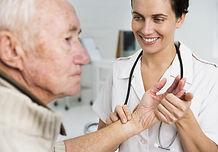 Nurse takes pulse of elderley man