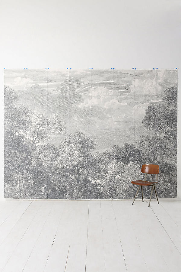 Towering trees and an endless sky cover your wall in graphite-hued forestry. An Anthropologie exclusive by Over & Over