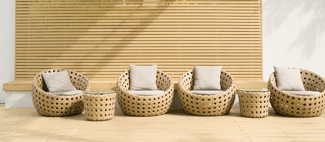 Wicker chairs on decking infront of wooden screen