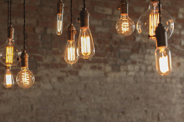 lightbulbs hanging against brick wall