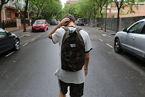A teenager walking a street