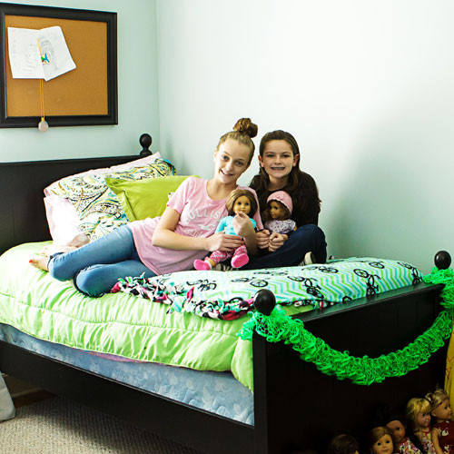 Two girls sitting on a bed with dolls