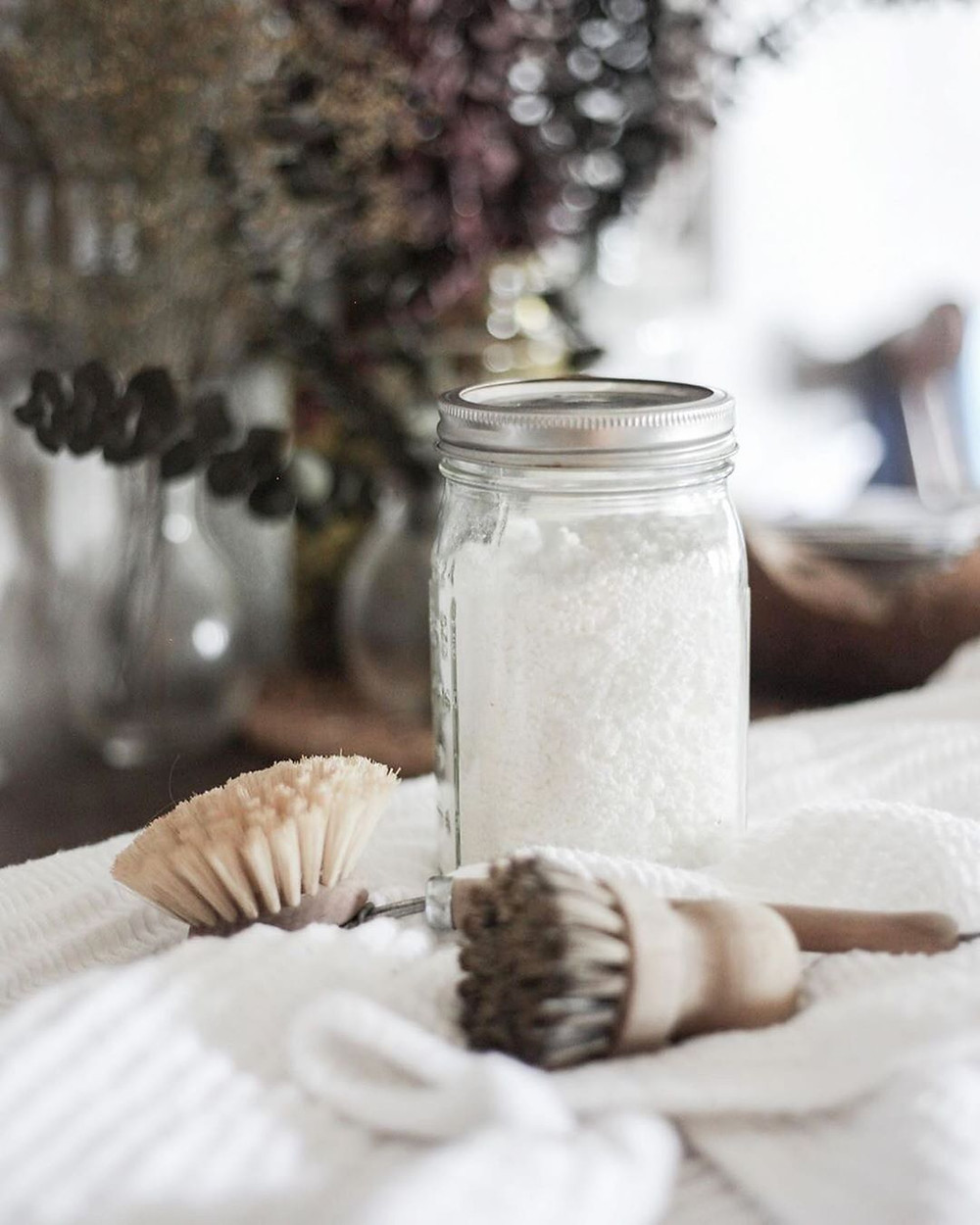 DIY Plastic-free Dishwasher Powder and Tablets in a glass jar against white background
