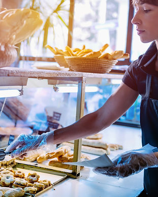 female-shop-assistant-arrange-pastry-in-