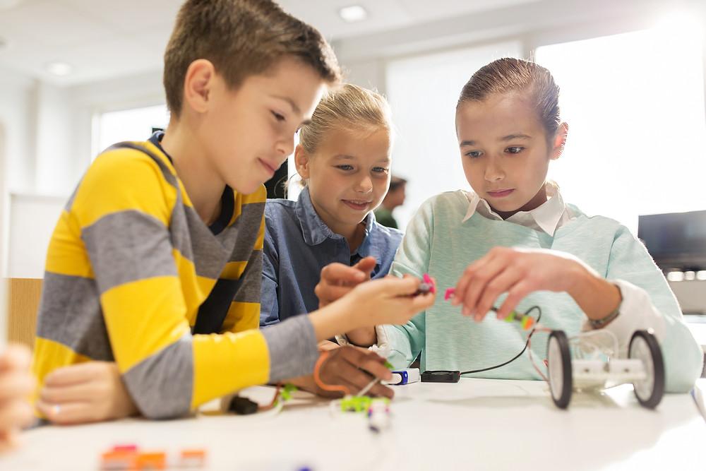 Niños y niñas haciendo robótica