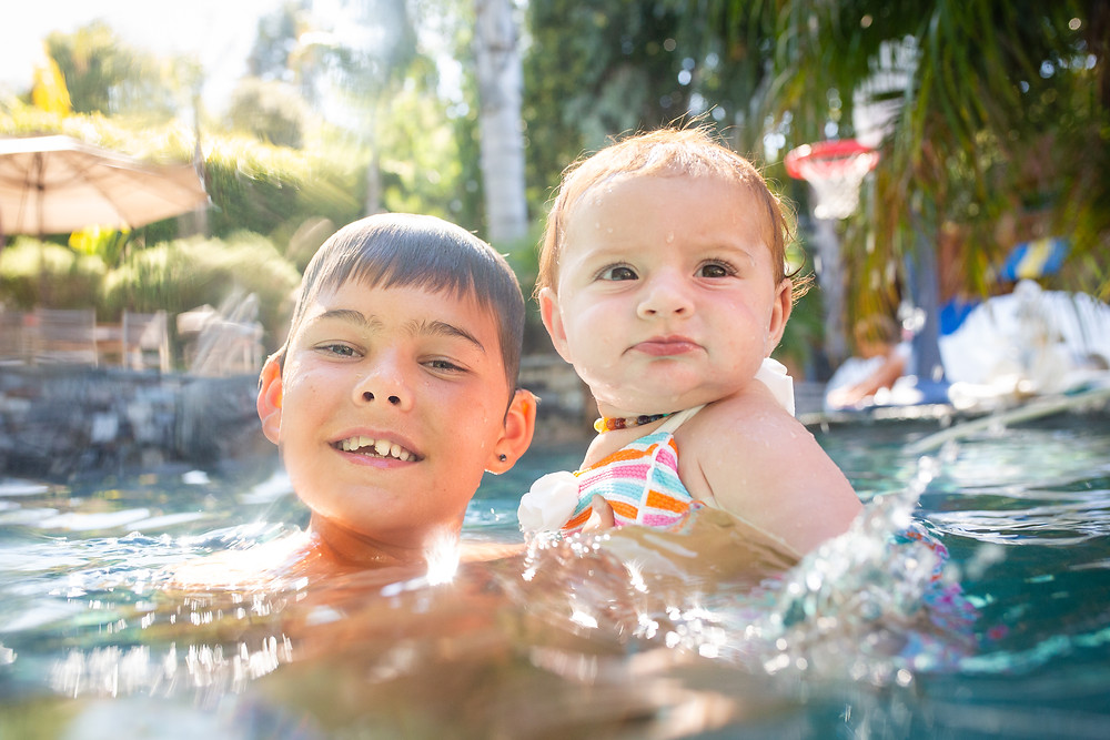 tween boy holding his baby girl cousin in a pool