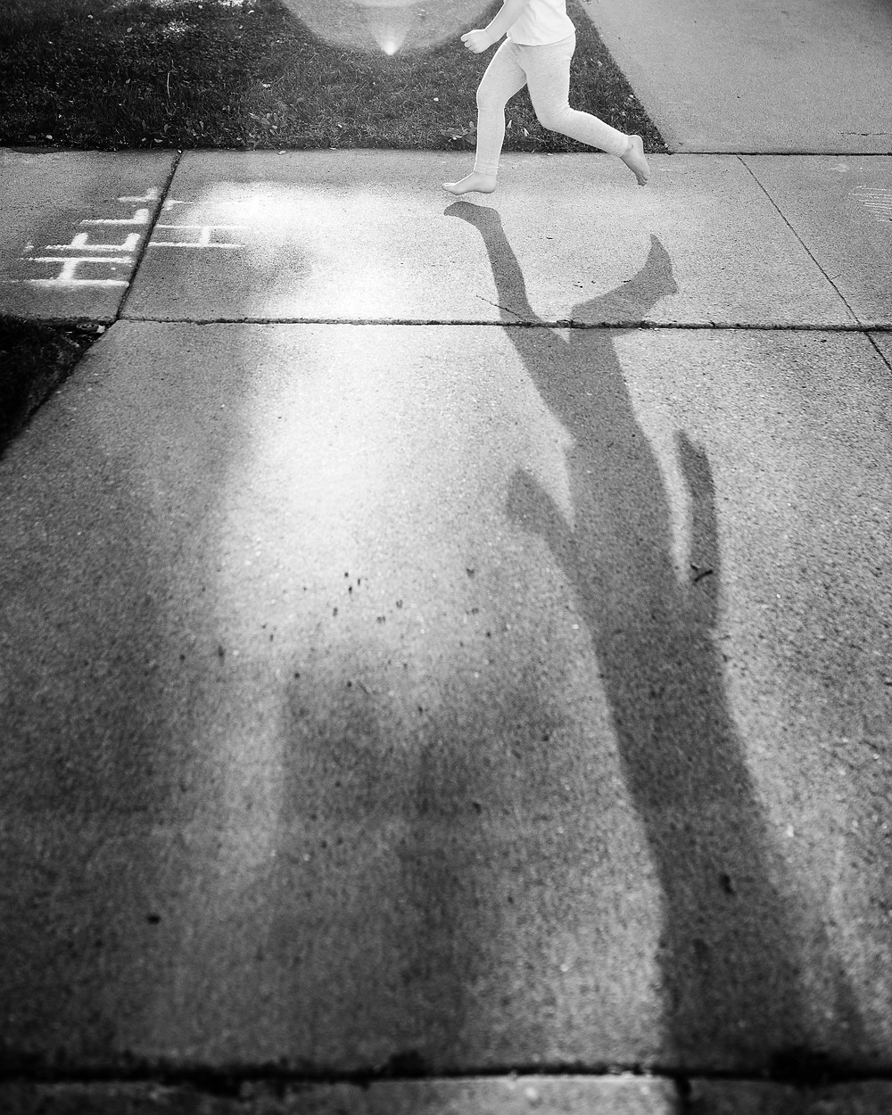 black and white photograph of a little girl skipping along a sidewalk with her shadow