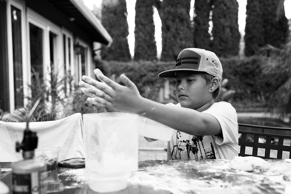 black and white image of a tween boy wearing a baseball cap making pizza dough