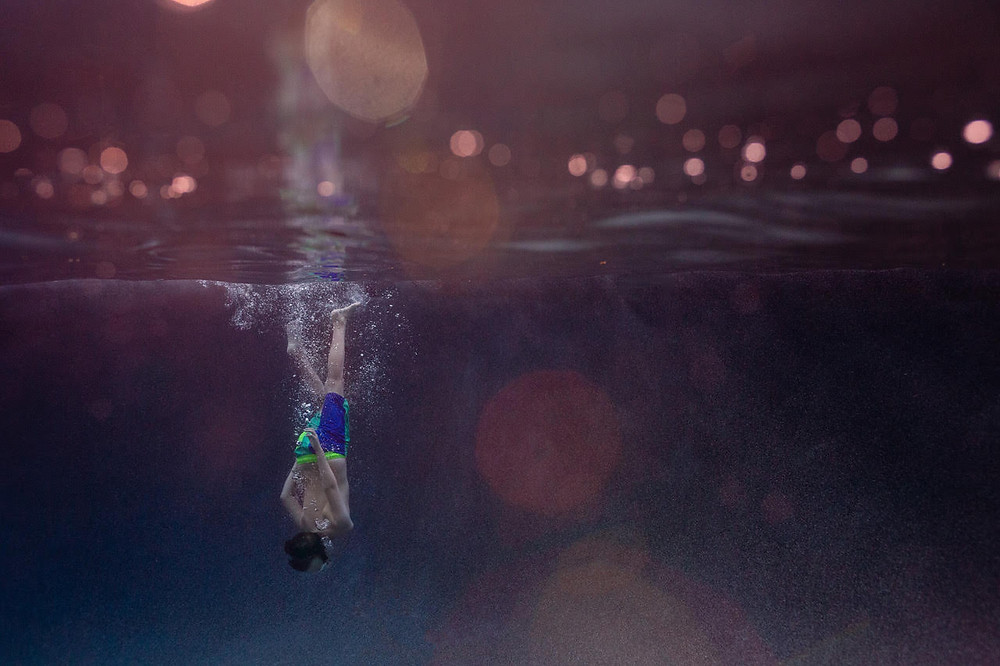 underwater image of a boy diving into water that appears deep