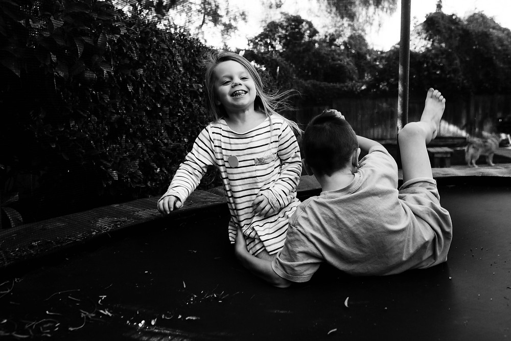 black and white image of a little girl laughing as she falls down on a trampoline; her brother's arm is around her as they fall together