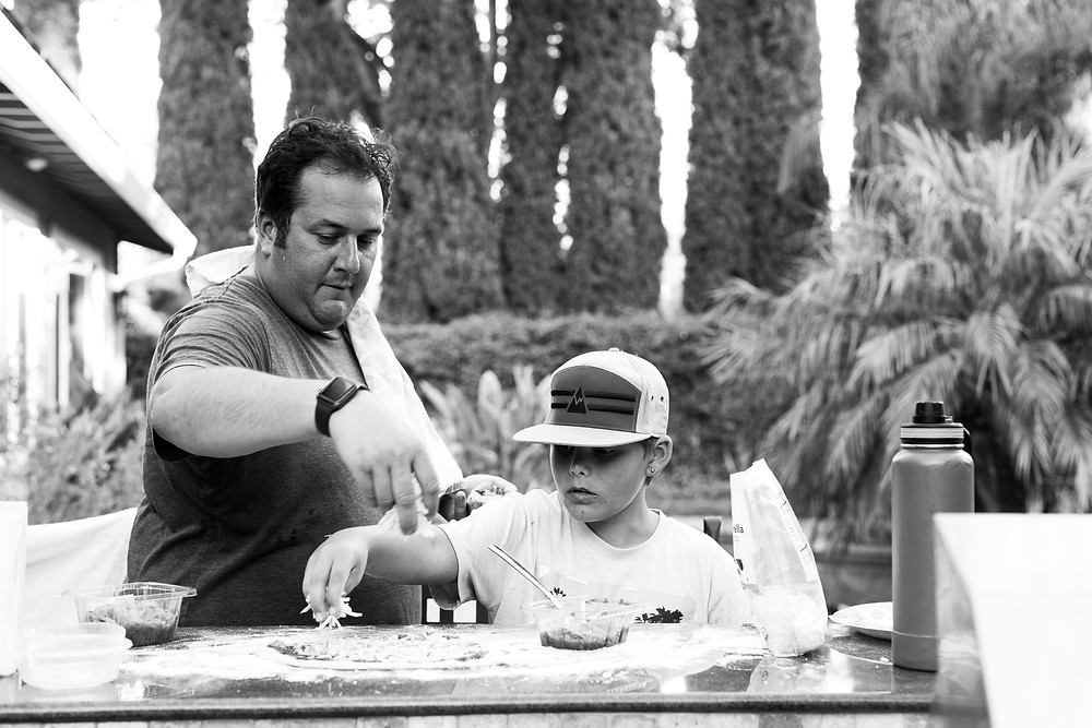 black and white image of an uncle and his nephew creating homemade pizza pies together