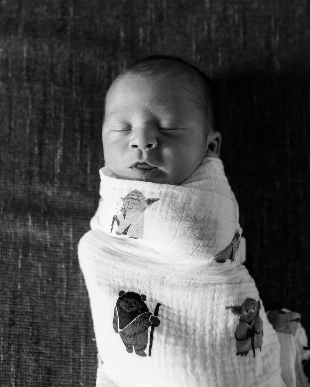 black and white image of a newborn baby boy with his mouth slightly open, wrapped in a Yoda and Ewok swaddle