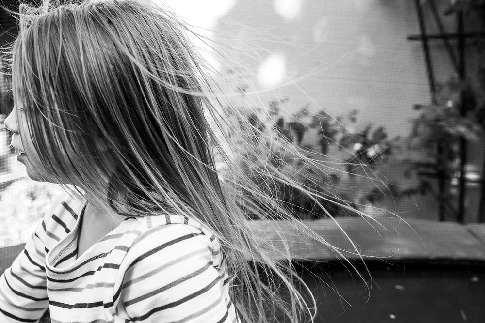 black and white image of a little girl wearing a striped shirt with her hair blowing in the breeze