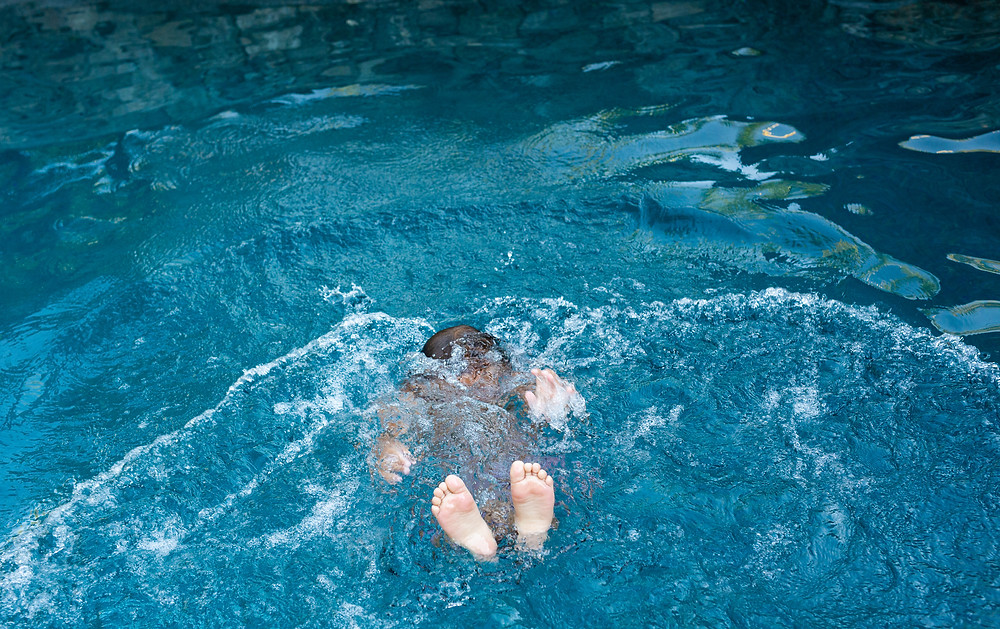 child dunking their whole body underwater in a pool