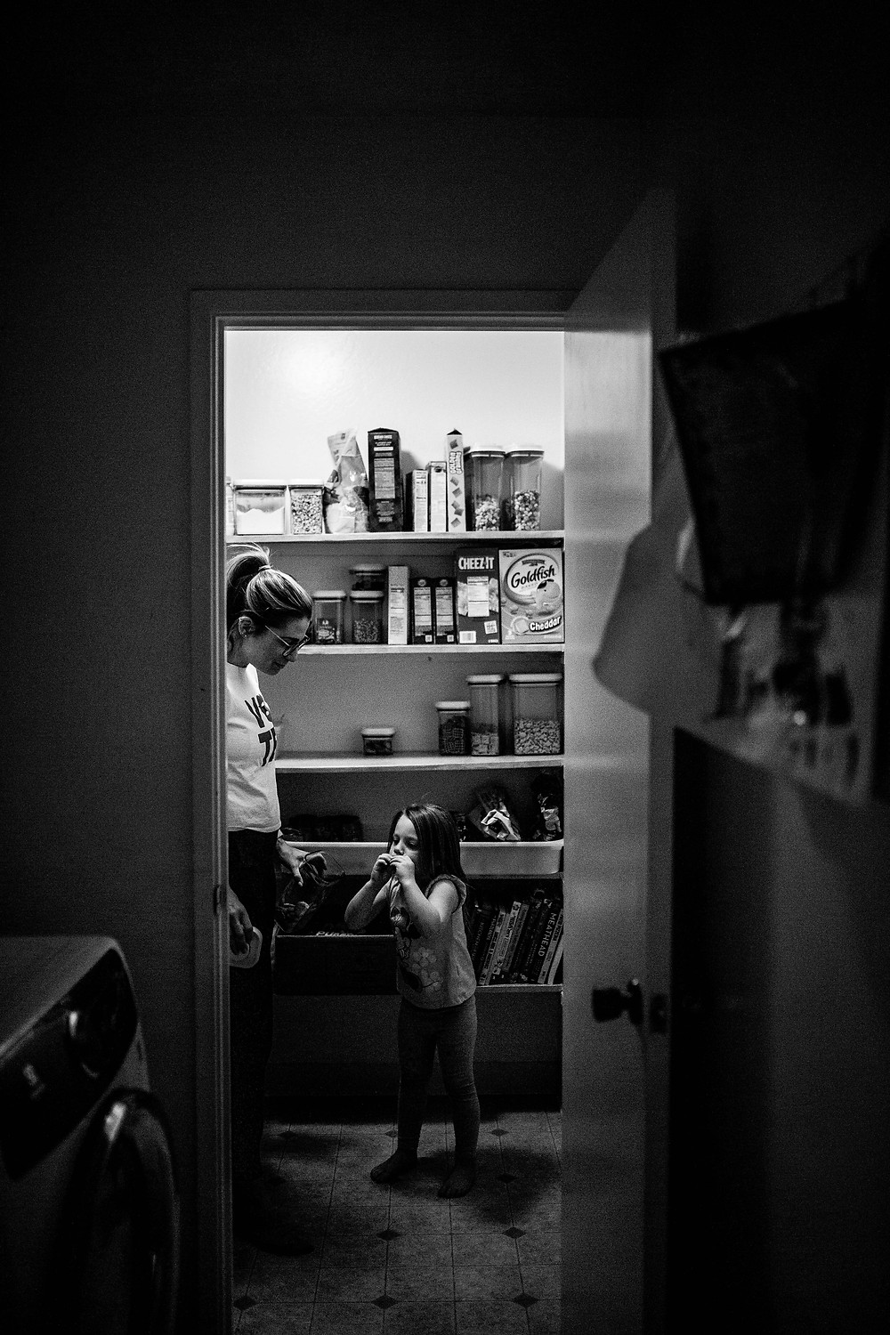black and white image of a mom with her hair in a ponytail helping her young daughter get a snack out of the pantry