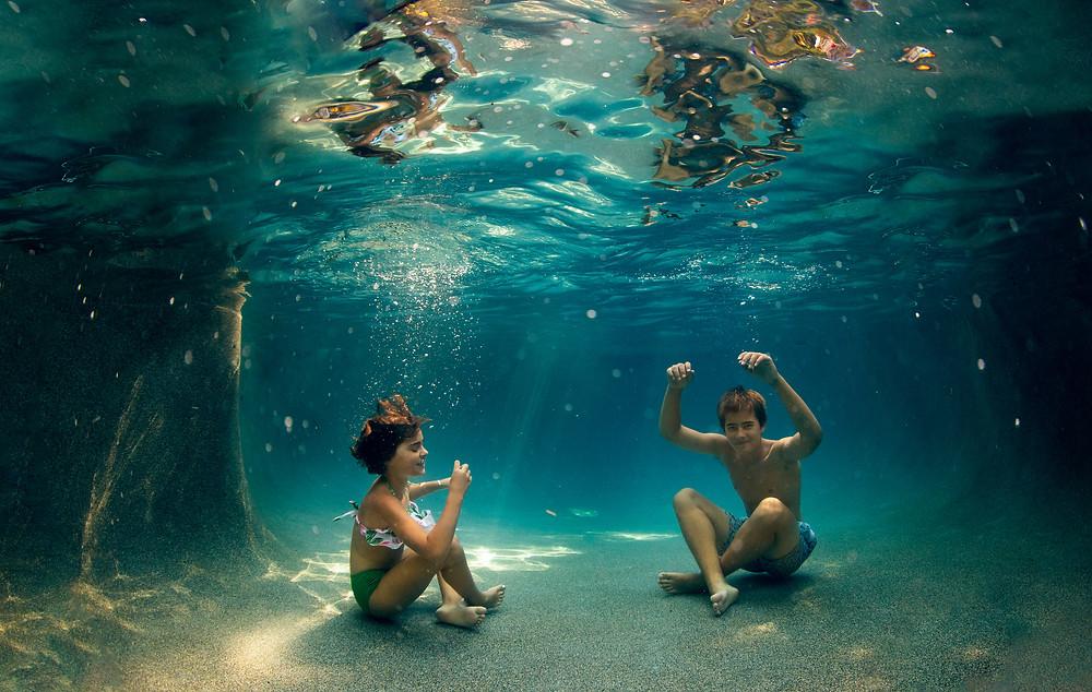 two tweens having fun sitting on the bottom of a pool