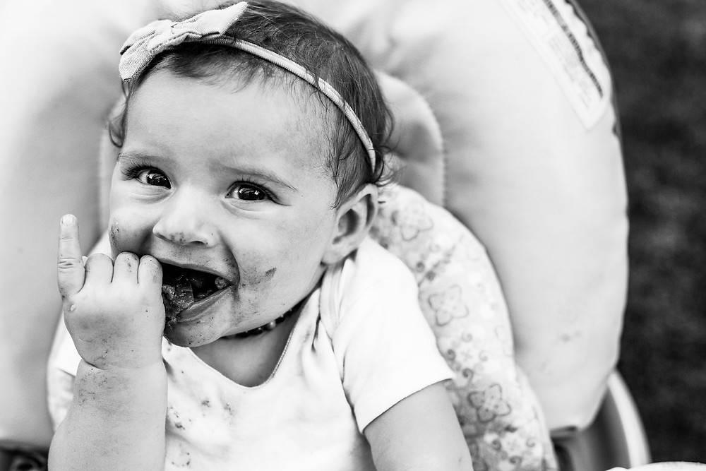 black and white image of a messy baby girl smiling and having pizza