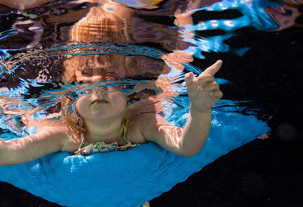 underwater image of a little girl on a pool noodle with a dark background