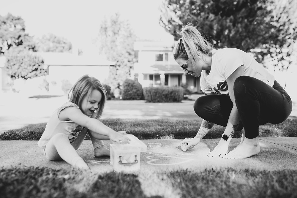 black and white picture of a little girl and her mom doodling with sidewalk chalk during the coronavirus pandemic in California