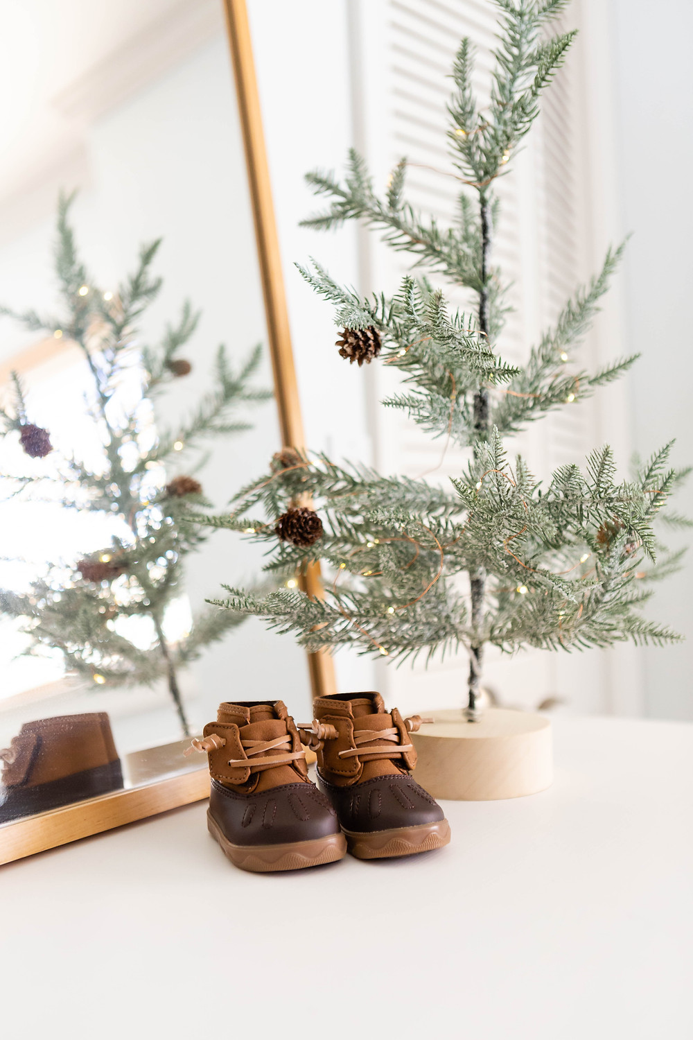 delicate sapling with fairy lights, baby duck boots, naturally framed mirror, California nursery decor