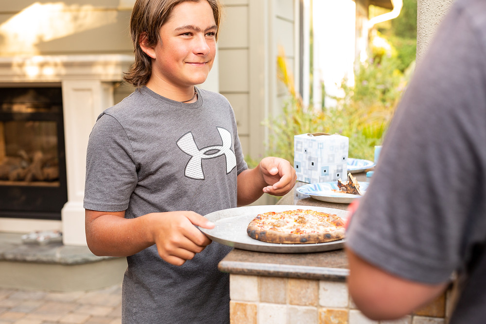 boy smiling up at his uncle as he holds a plate with homemade pizza on it, Under Armour tee