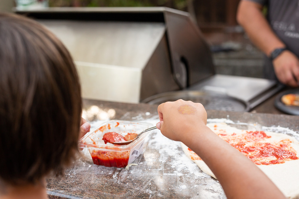 closeup of making homemade pizza on a summer evening with family