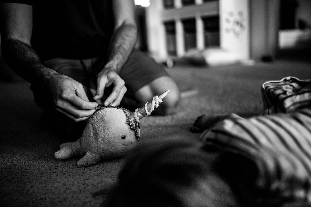 black and white image of a dad's hands fixing jewelry onto a Jellycat narwhal as his daughter looks on from the foreground