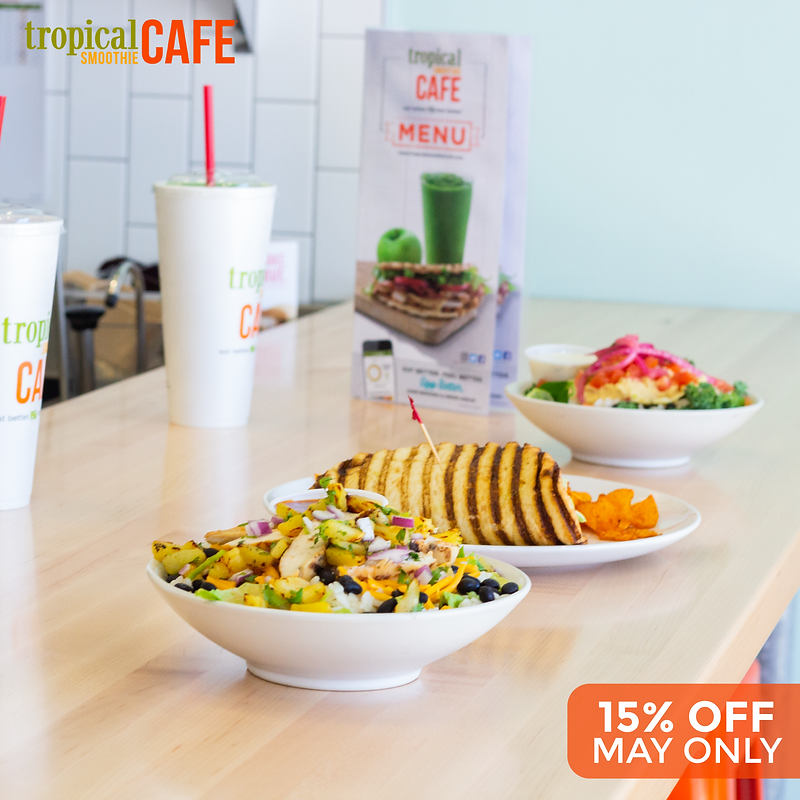 A photo taken of tropical smoothie cafe, it contains their branded drink cups and a food wrap.