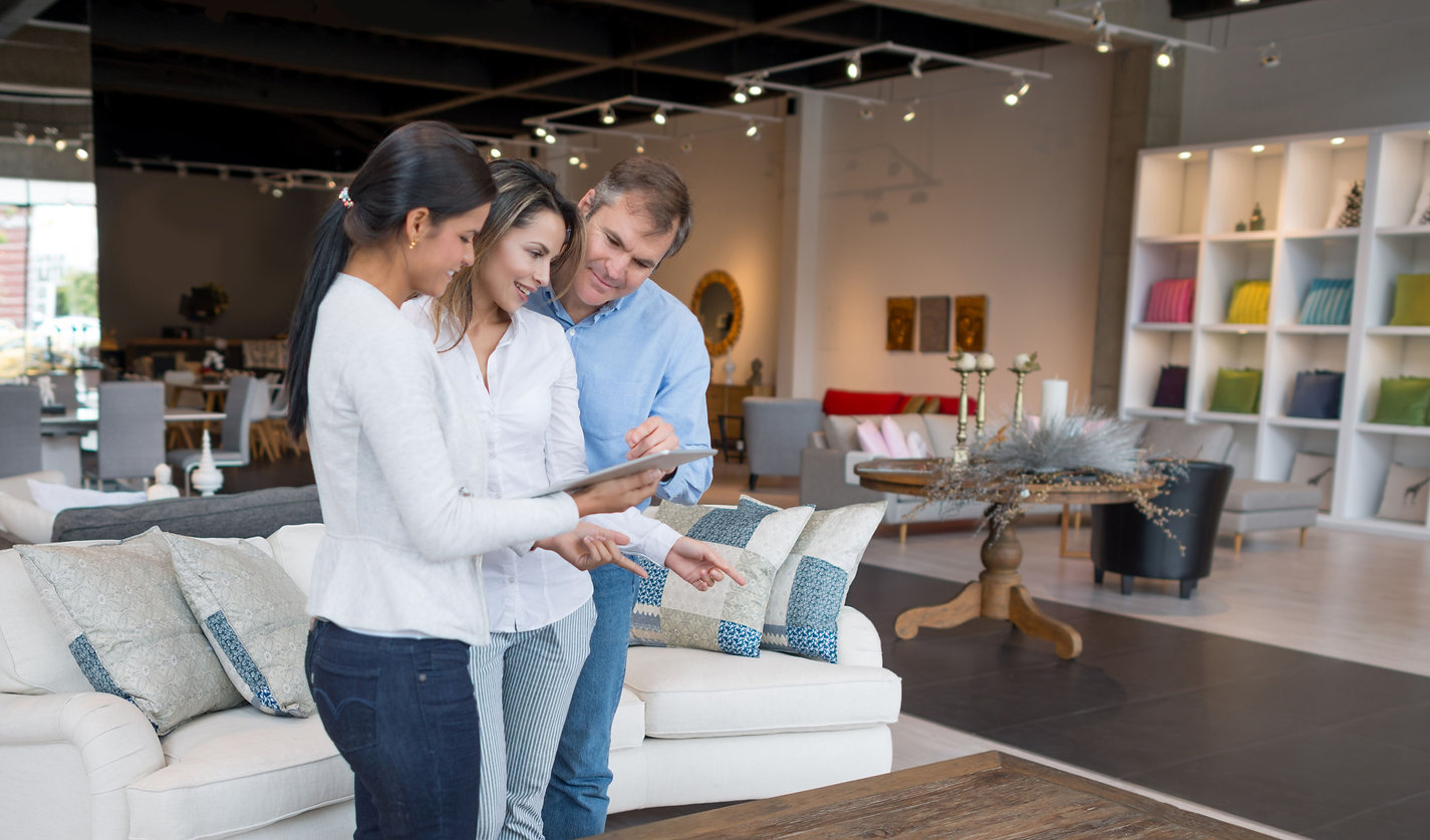 This is an image of a couple looking over the employees ipad while pointing at furniture they are going to buy.