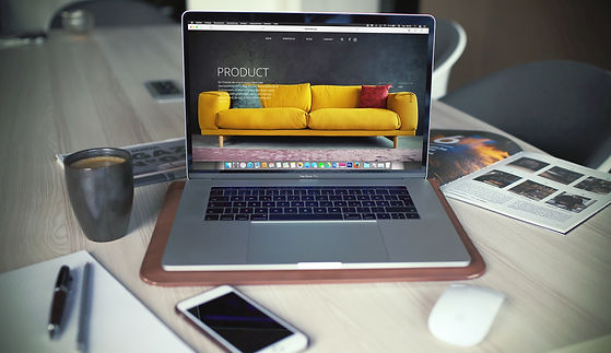 An image of a macbook showing a website. The macbook is on a table with a magazine, coffee, stationary and a mobile phone.