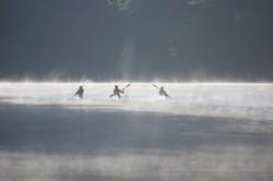 Drie kayakken in de mist