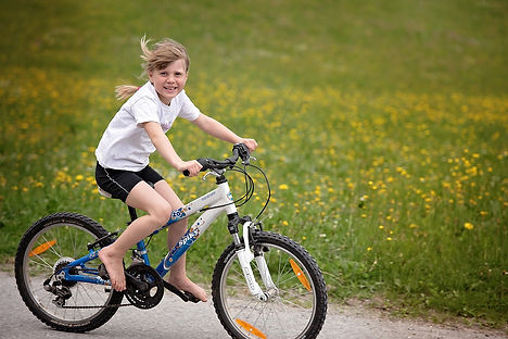 Young girl on bicycle riding through a nature scene.
