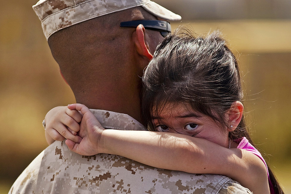 Image of a scared looking little girl hugging a soldier in camoflauge