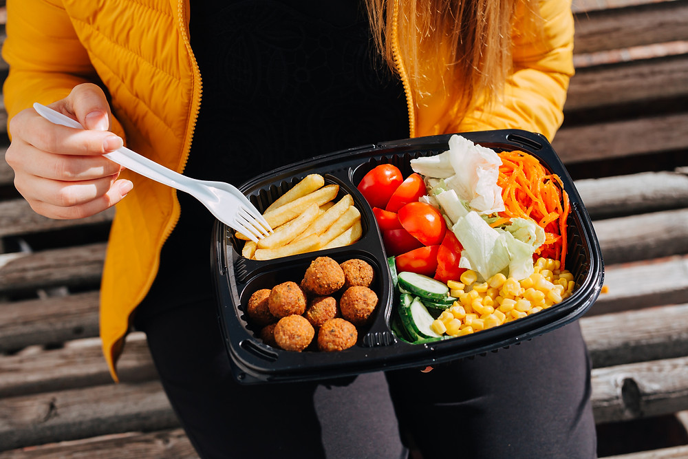 female athlete sitting outside eating healthy takeout food while on the road