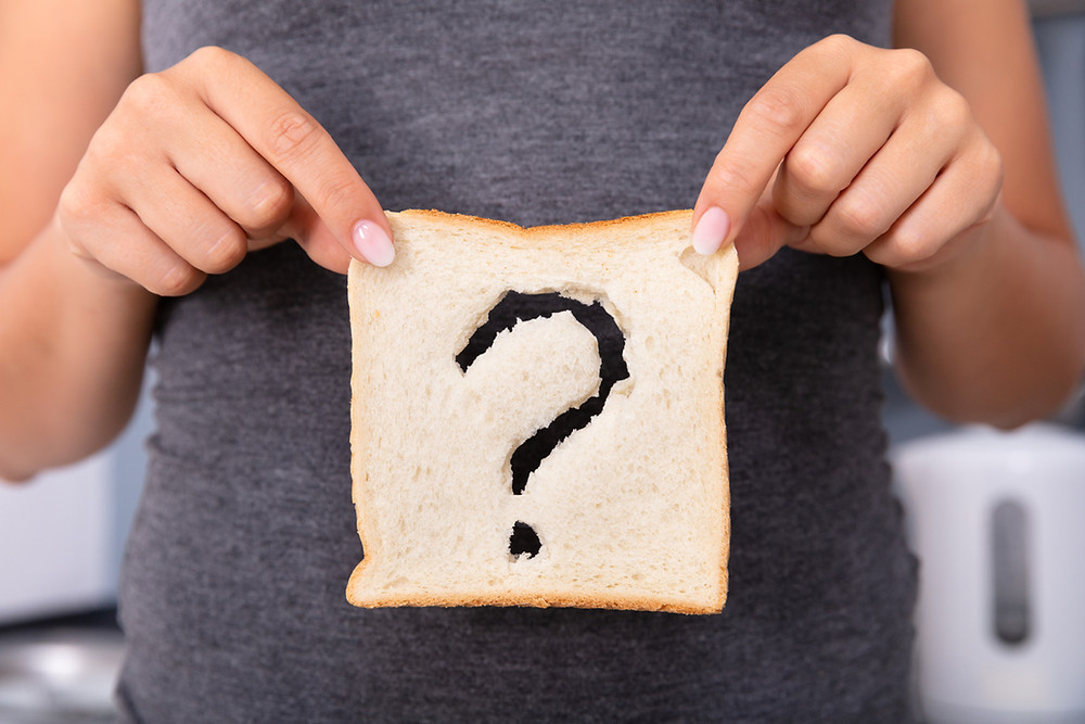 Woman holding a slice of bread with a question mark in it