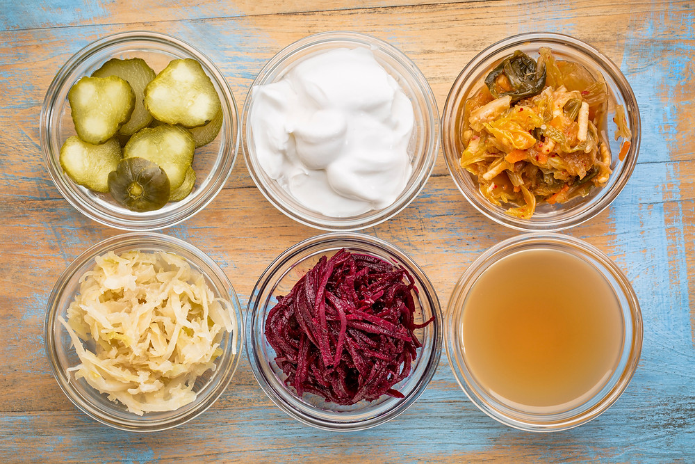 A variety of fermented food and drinks. Top view against a stone countertop: fermented cucumbers or pickles, kefir, kombucha, sauerkraut, miso soup, tempeh, natto, kimchi, yogurt, mozzarella cheese, gouda cheese and cottage cheese.