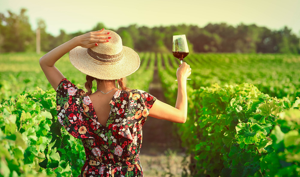 Young woman in floral dress wearing hat and holding a glass of red wine in sunny vineyard