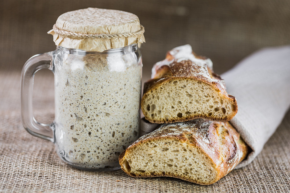 Freshly baked sourdough bread wrapped in a bread bag and pictured with a greatly fermented sourdough starter sealed in a mason jar.