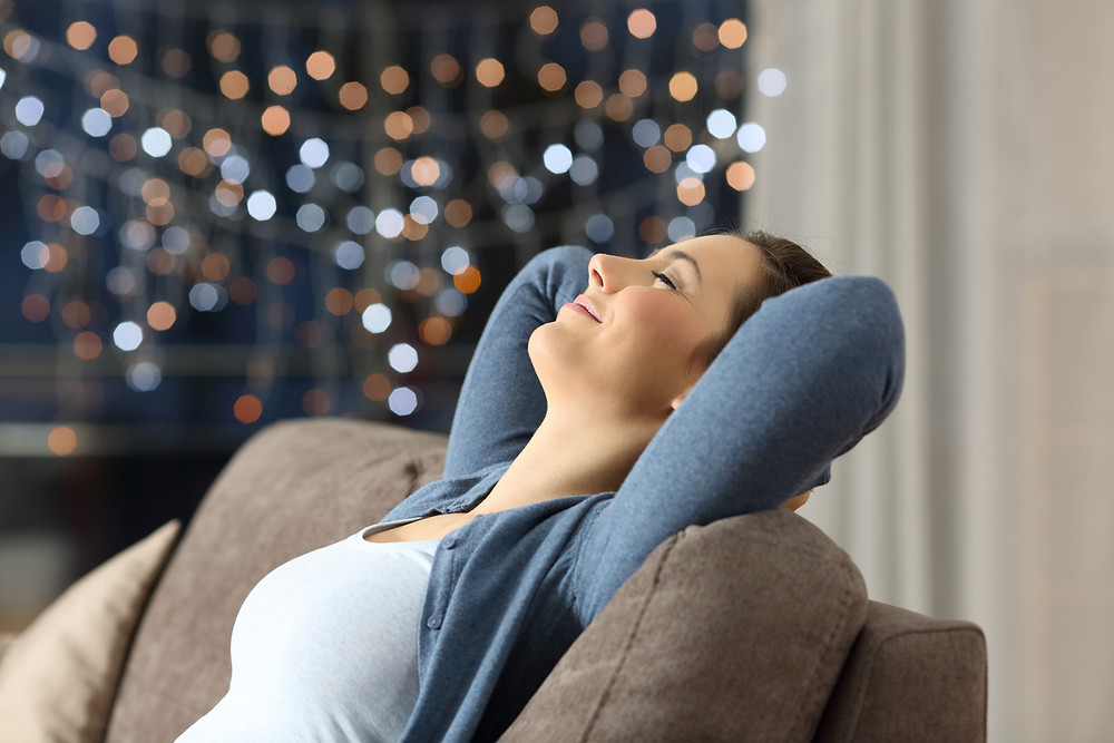 woman relaxing on couch at night with holiday lights in the background
