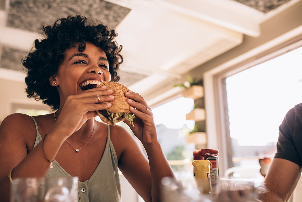 young woman happily eating hamburger, healthy relationship with food