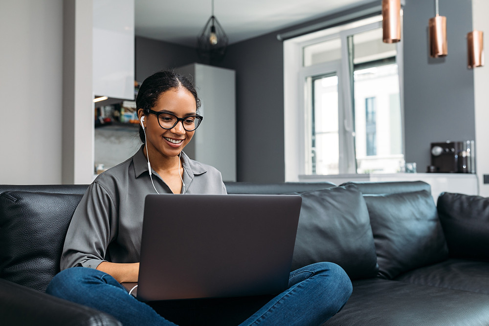 young woman on laptop with one headphone in sitting on couch happily working from home