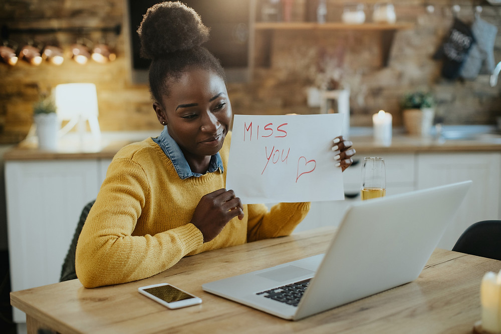 """young woman sitting in kitchen on virtual call holding up sign that says """"miss you"""""""