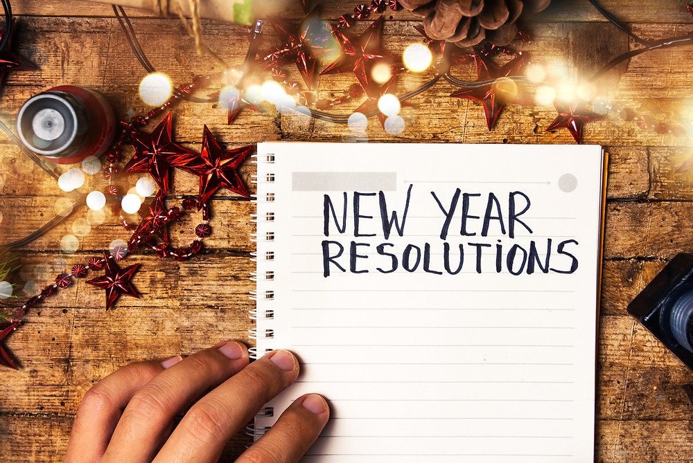 "Notepad on festive desk with sheet titled ""New Year Resolutions"""
