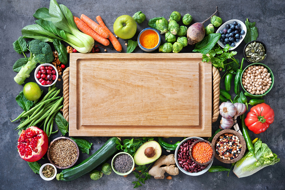 An assortment of fresh fruit, vegetables, legumes, nuts, and seeds surrounding a cutting board.