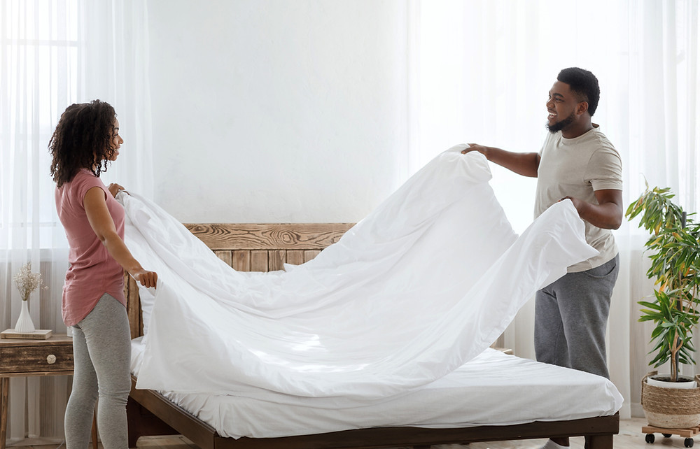 Young couple in bright room happily making the bed in the morning together with clean white linens