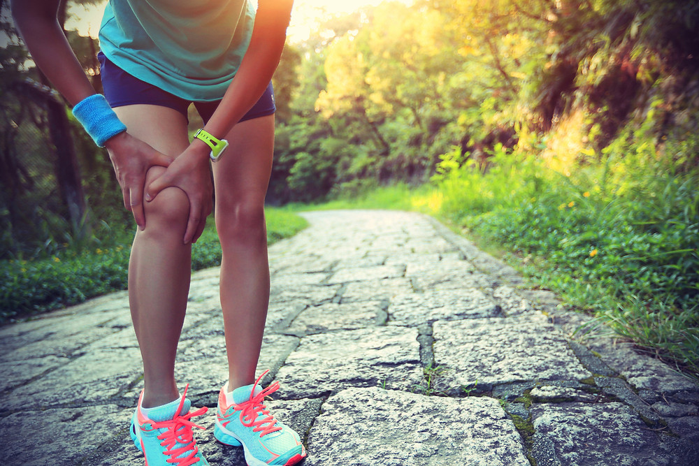 young woman holding knee, with pain in knee on a run